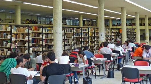 Uma sala de leitura em uma biblioteca. De um lado, estantes de livros. De outro lado, mesas com estudantes lendo.