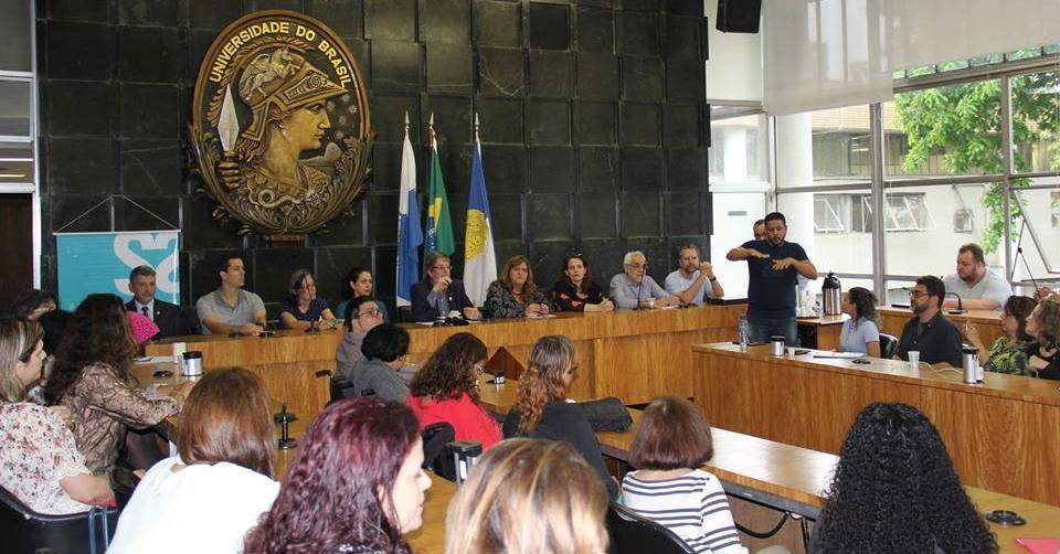 Sessão de plenária da Universidade Federal do Rio de Janeiro. Pessoas assistem sentadas enquanto um intérprete faz tradução de libras.