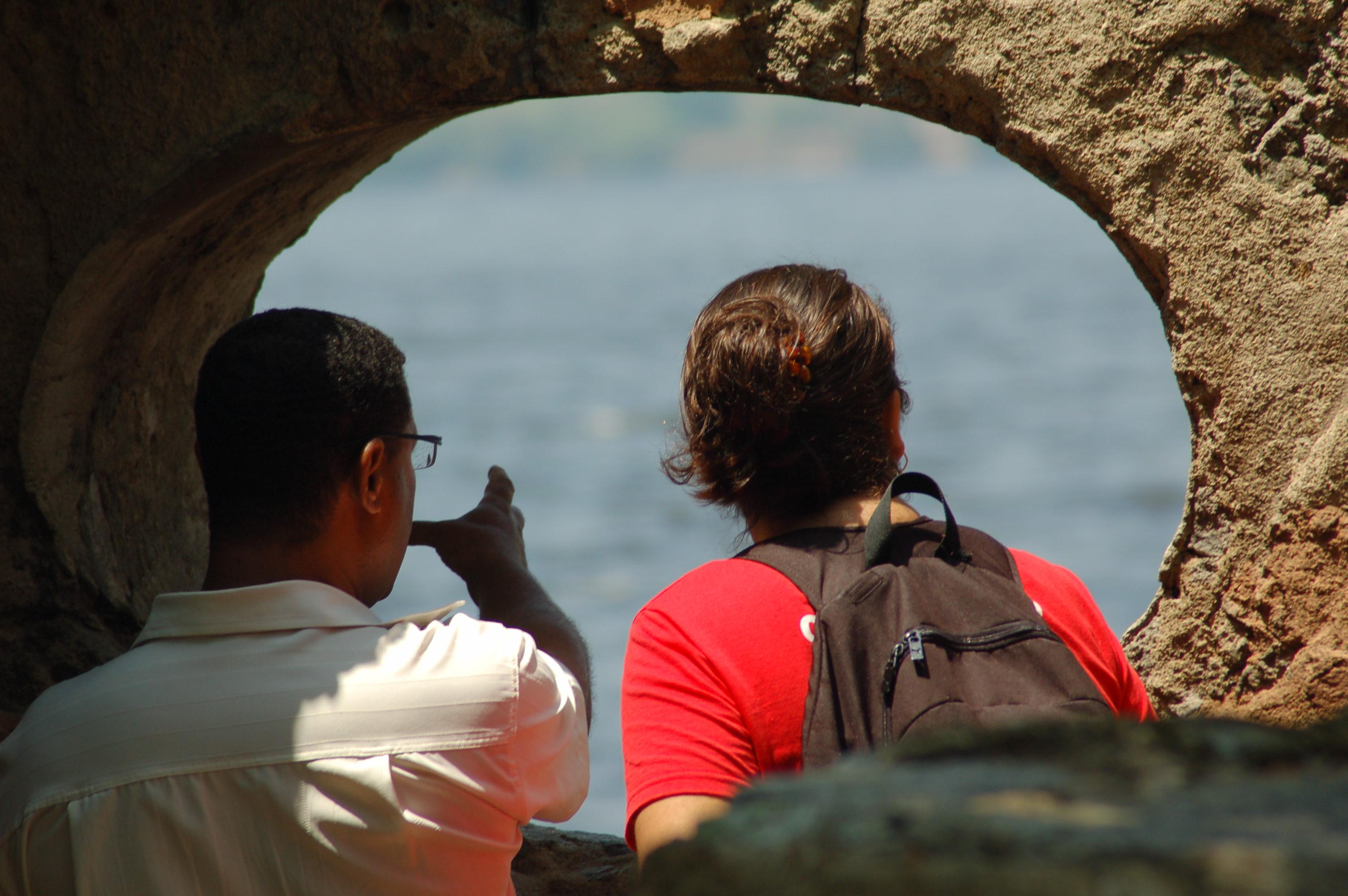 Imagem ilustrativa de duas pessoas em ambiente externo conversando. Estão na ilha do Catalão na Baia da Guanabara em frente a uma abertura circular numa parede de ruína que dá vista à baia de guanabara. Uma das pessoas aponta para a baía com a intenção de explicar algo e a outra pessoa demonstra interesse na explicação. A imagem faz uma metáfora com a explicação que daremos a seguir nesta página sobre a audiodescrição e sobre como uma pessoa com deficiência visual pode