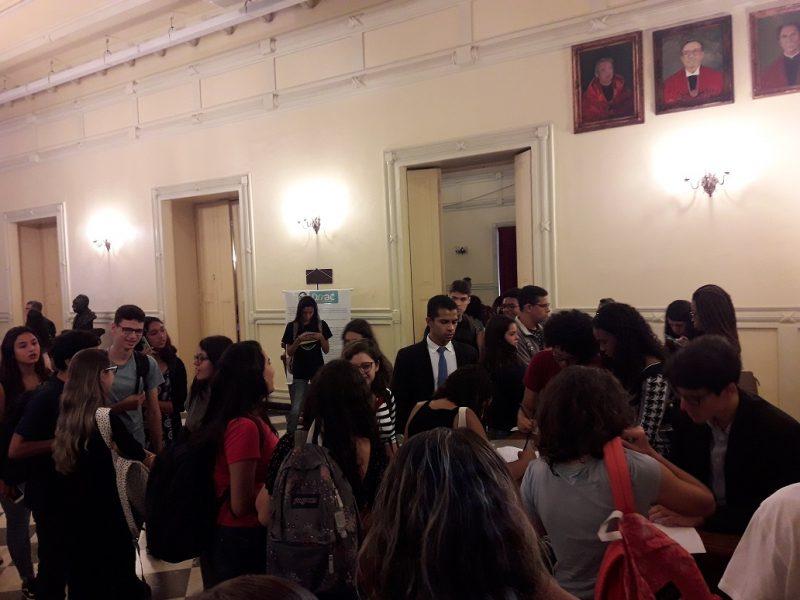 Foto de pessoas reunidas na entrada do Salão Nobre da Faculdade Nacional de Direito, assinando lista de presença do Dia da Acessibilidade na FND/UFRJ.